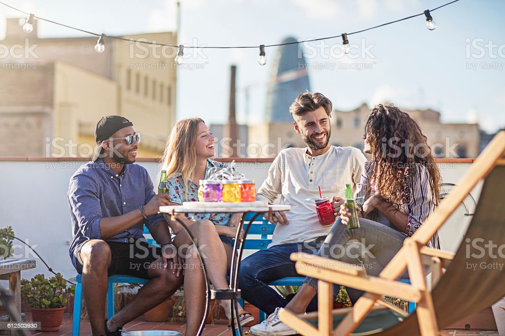 Group of friends having a drink at rooftop party - foto de stock