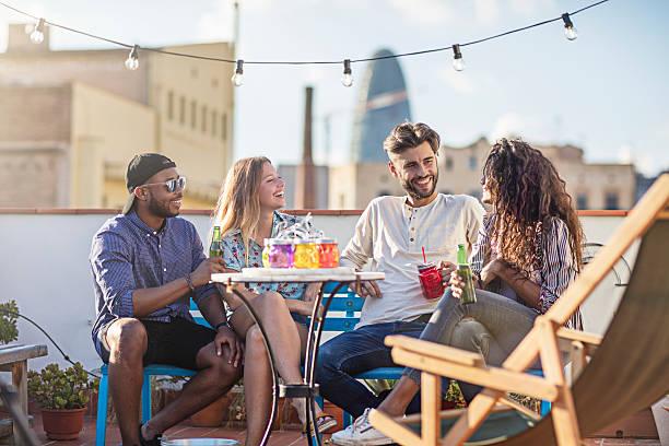group of friends having a drink at rooftop party - spain solar bildbanksfoton och bilder
