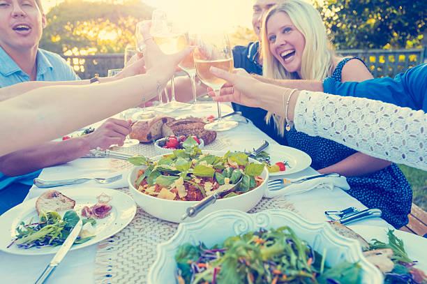 gruppe von freunden, die eine mahlzeit im freien. - partysalate stock-fotos und bilder
