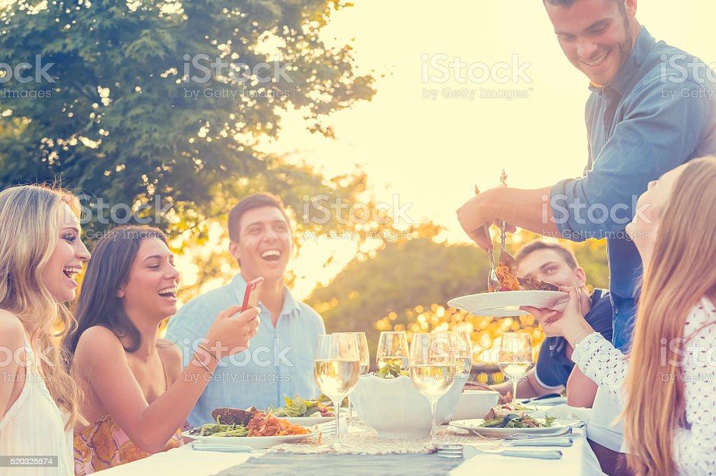 Grupo de amigos ter uma refeição ao ar livre. - foto de acervo