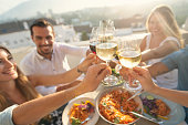 istock Group of friends having a meal outdoors. They are celebrating with a toast using wine. 1301470994