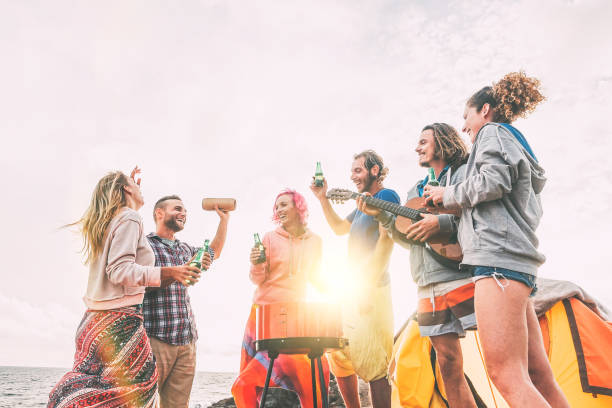Group of friends having barbecue drinking beers while camping on the beach - Happy people enjoying camp bbq playing guitar, singing and listening music at sunset -  Friendship, adventure concept stock photo