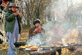 冬の早朝にキャンプ場で朝食を食べる友人のグループ