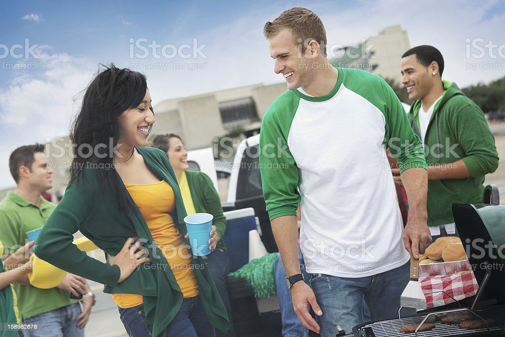 Group of friends having cook-out at college football stadium; tailgating stock photo