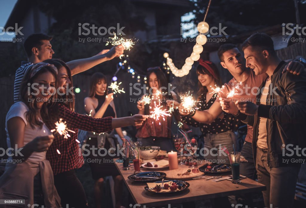 Group of friends having dinner party in backyard stock photo