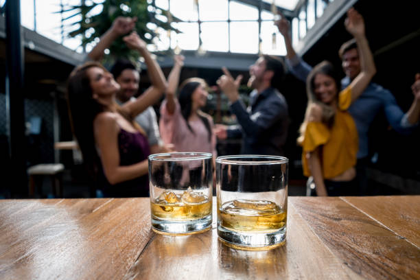 group of friends having drinks at a bar - whiskey stock photos and pictures