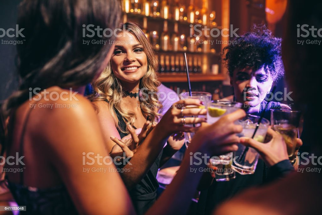 Group of friends having drinks at night club stock photo