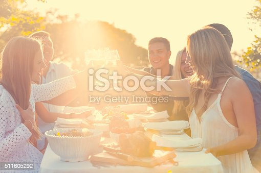 Group of friends having drinks at sunset. They are celebrating with a wine toast. There is food on the table including fruit and cheese. They are smiling and happy. Lens flare