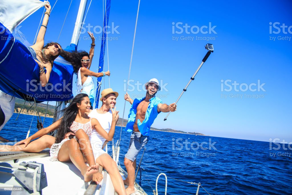 Group of friends having fun and making selfie on yacht stock photo