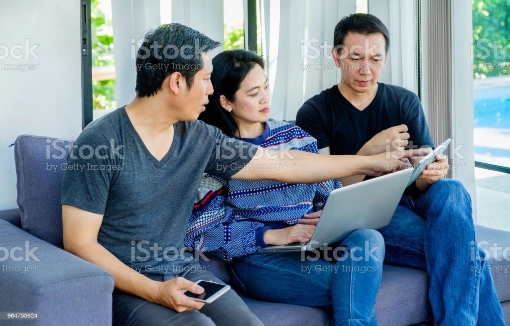 Group of friends having fun and using digital device (mobile,laptop,tablet) at home,Friendship concept. royalty-free stock photo