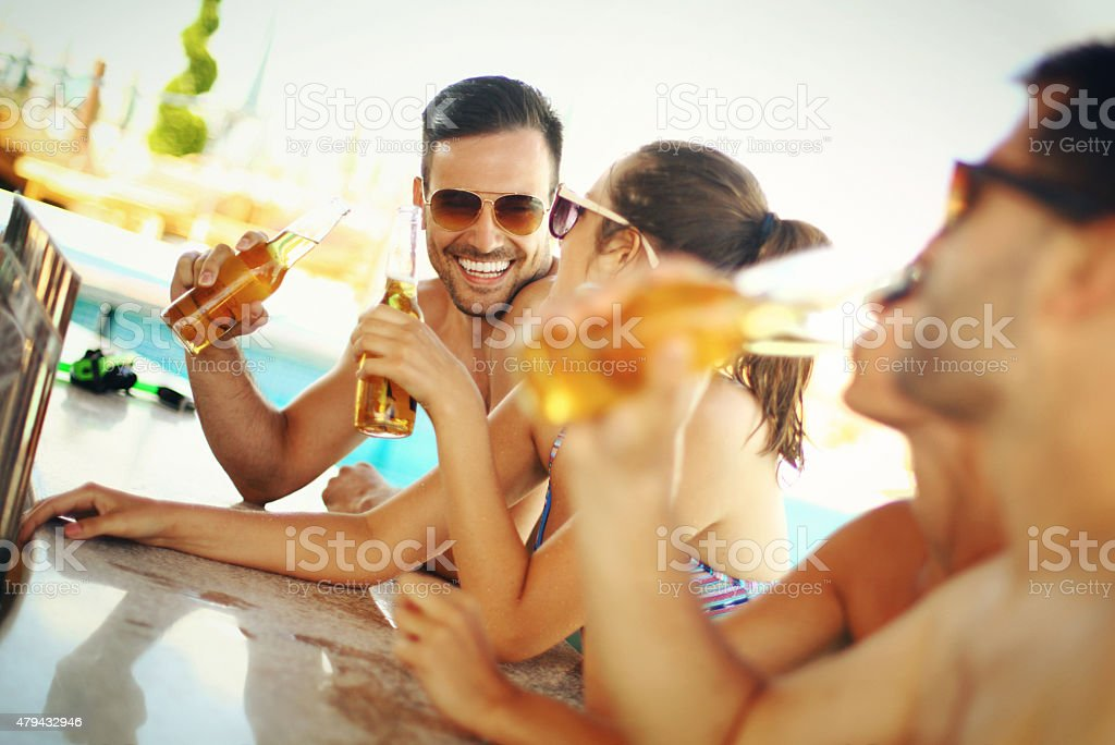 Group of friends having fun at beach bar. stock photo
