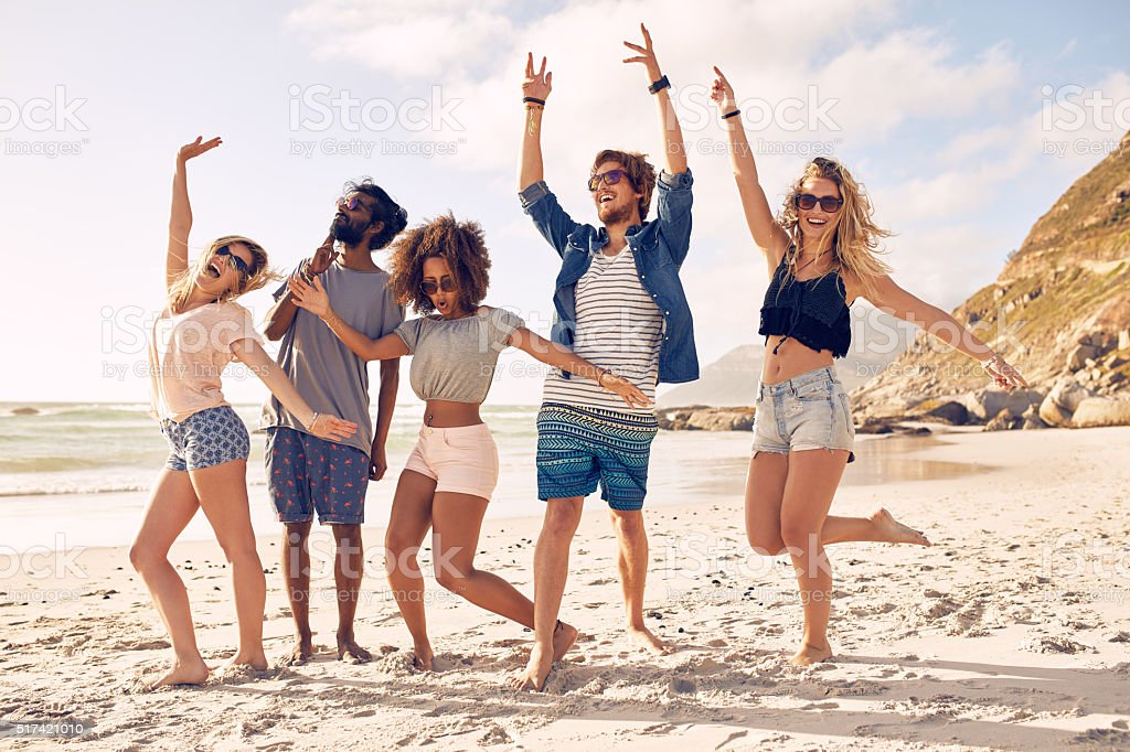 Group of friends having fun at beach Portrait of excited young friends standing on the beach. Multiracial group of friends enjoying a day at beach. Adult Stock Photo