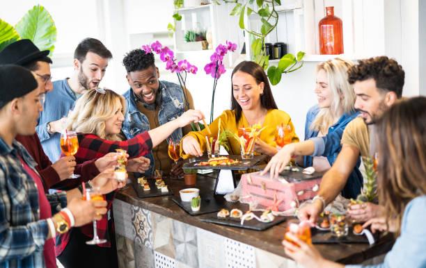 저녁 식사 전 파티 식전주 뷔페에서 칵테일을 마시고 간식을 먹는 친구 그룹 - 집에서 함께 시간을 보내는 젊은이 - 자연 인테리어 조명이있는 밝은 생생한 필터 - 식전 반주 뉴스 사진 이미지