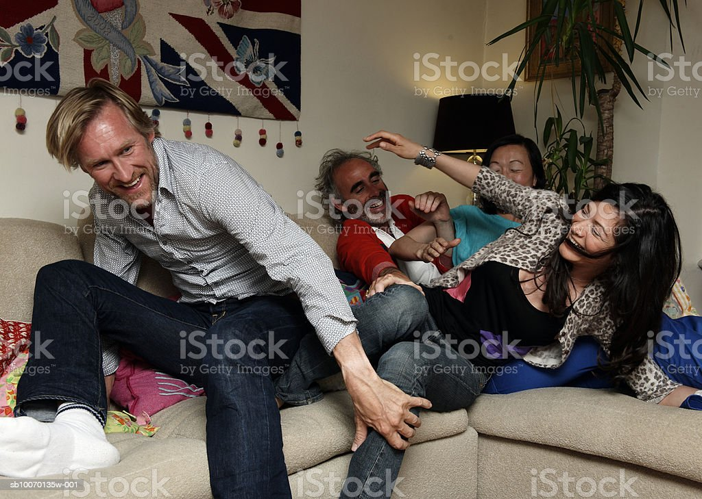 Grupo de amigos, divertir-se na sala de estar foto de stock royalty-free