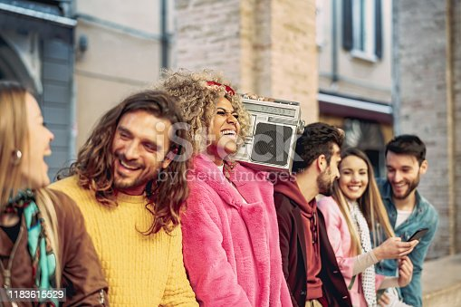 861023492 istock photo Group of friends having fun listening music with vintage boombox - Happy young people making party outdoor  - Youth culture and millennial lifestyle concept 1183615529