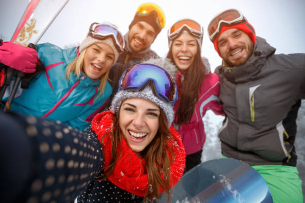 Group of friends having fun on the snow and making selfie stock photo