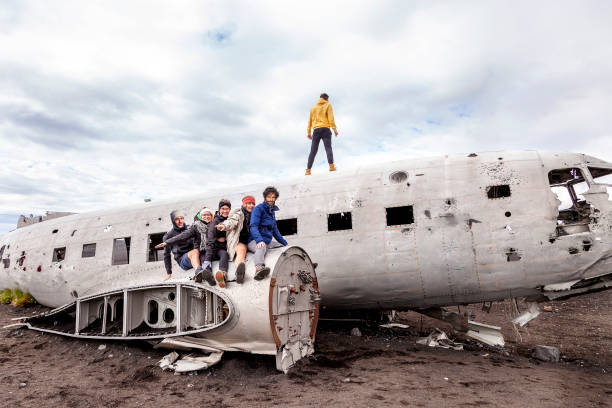 group of friends having fun over a plane group of friends having fun walking over the wreck of a plane in Iceland sólheimasandur stock pictures, royalty-free photos & images