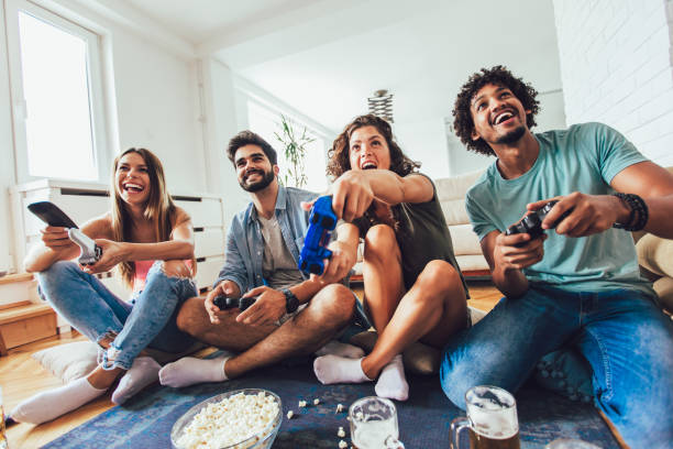 Group of friends having fun playing video games at home. stock photo