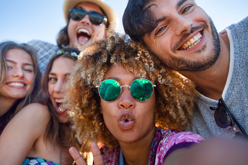 Group of friends having fun taking a selfie. They are all looking at the camera and smiling and laughing. Some are making funny faces. Background is blue sky on a sunny day.