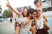 Group of young friends having fun time at music festival