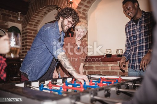 Group of friends enjoying their time, while playing Foosball in the pub