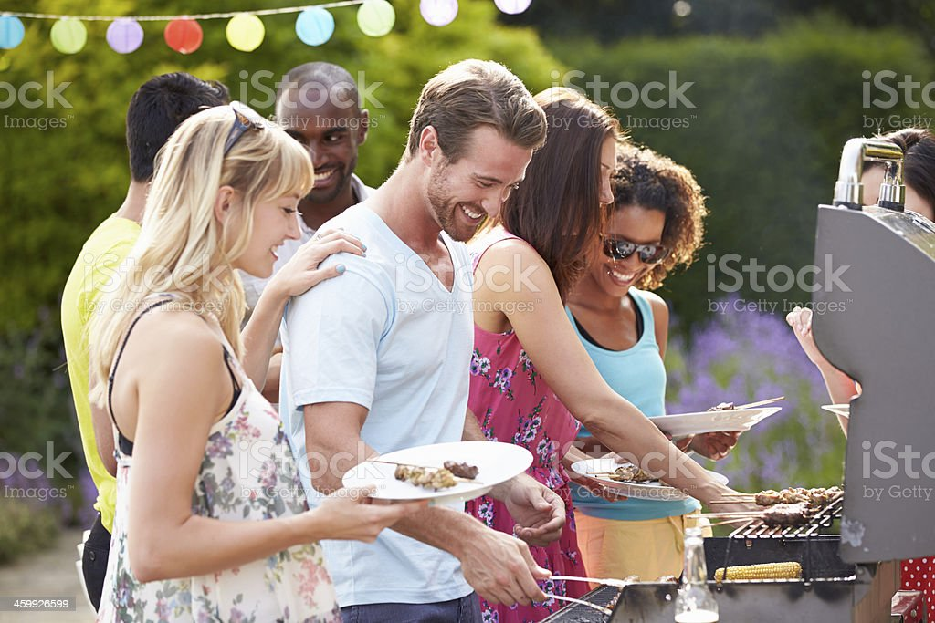 Group Of Friends Having Outdoor Barbeque At Home​​​ foto