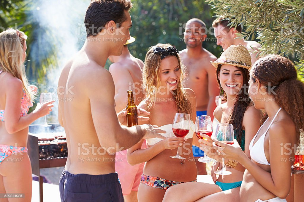 Group Of Friends Having Party By Swimming Pool stock photo