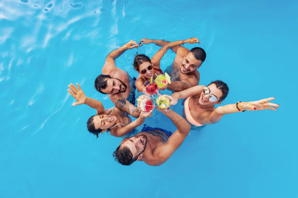 Group of friends having party in pool stock photo