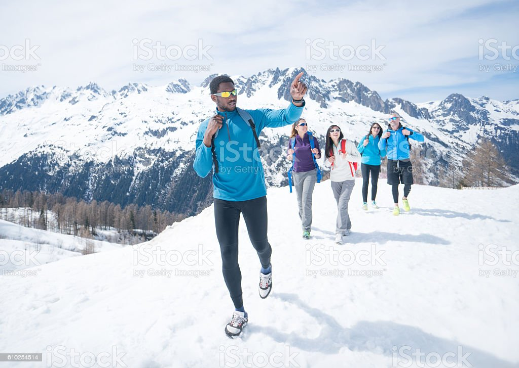 Group of friends hiking in the snow stock photo