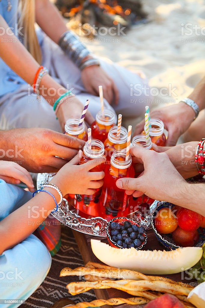 Group of friends holding drinks at the summer picnic stock photo