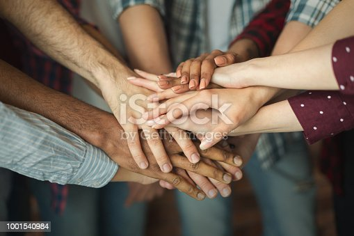 Friendship and teamwork. Multiethnic company of friends stacked hands together, copy space