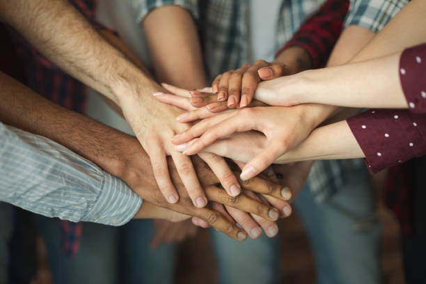 group of friends holding hands together - armonia foto e immagini stock