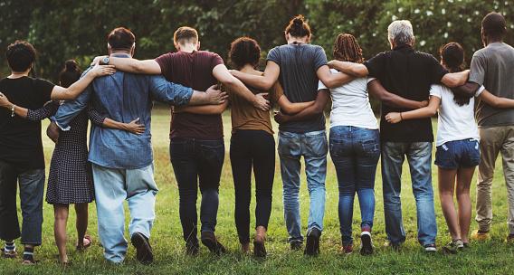 Group Of Friends Huddle In Rear View Together - zdjęcia stockowe i więcej obrazów Codzienne ubranie