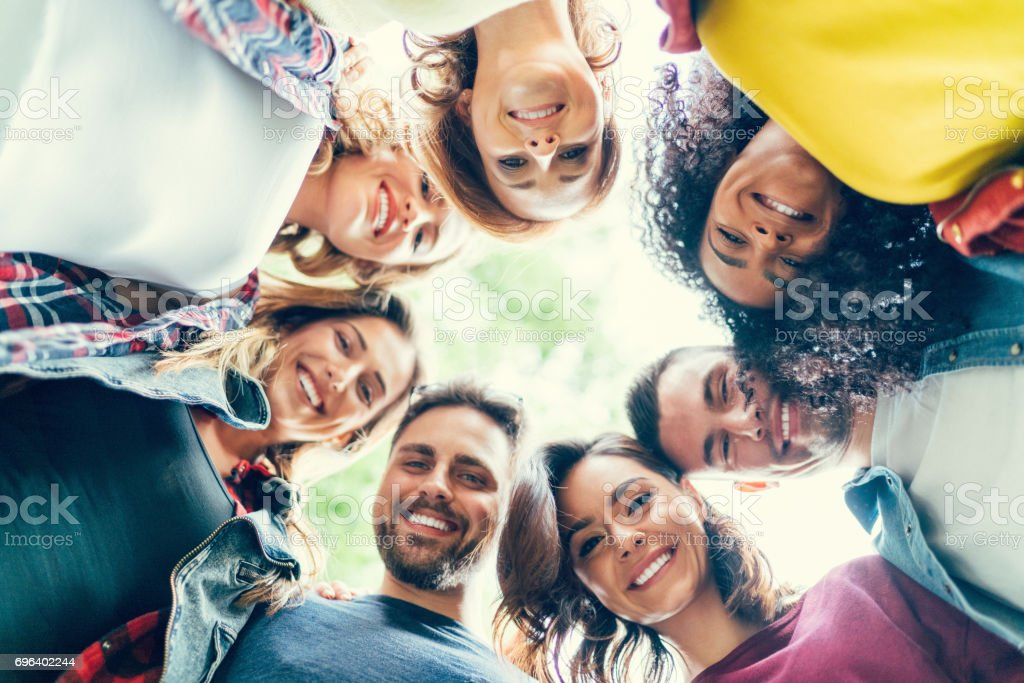 Group of friends in a circle smiling stock photo