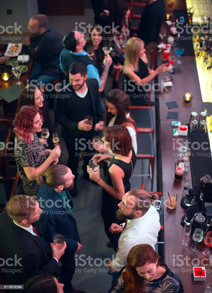 Group of friends in bar having drinks stock photo