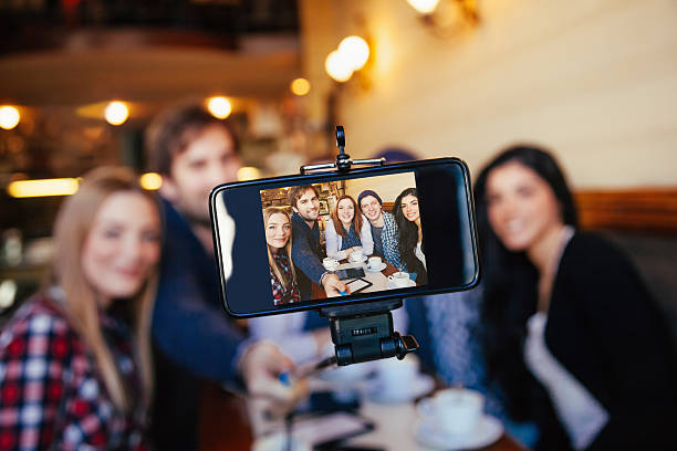 Group Of Friends In Cafe Taking Selfie stock photo