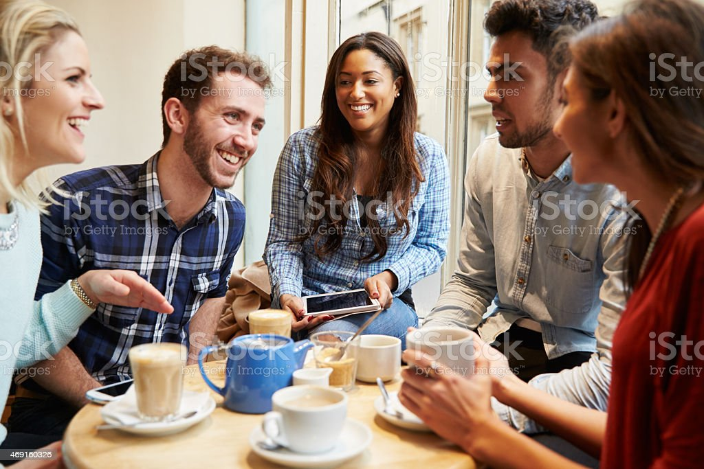 Group of friends in cafe using digital devices stock photo