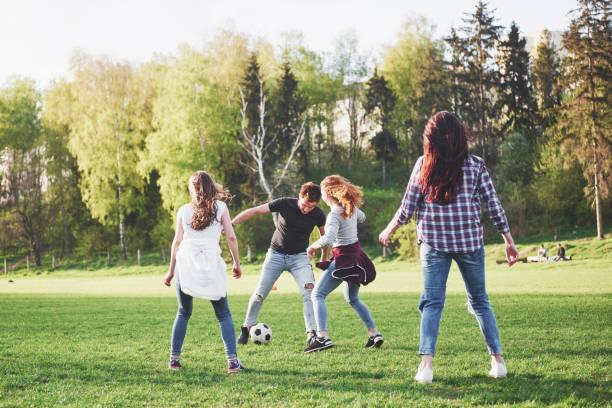 Eine Gruppe von Freunden im lässigen Outfit spielt Fußball im Freien. Die Leute haben Spaß und Spaß. Aktive Erholung und landschaftlicher Sonnenuntergang – Foto