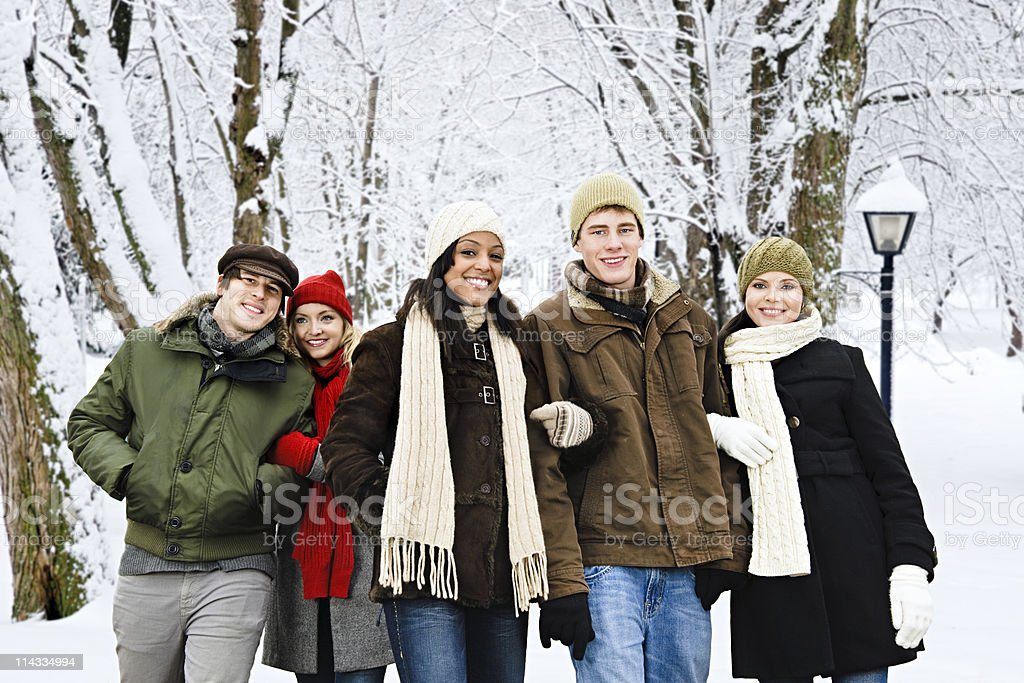 Group of friends in coats outside in winter snow royalty-free stock photo