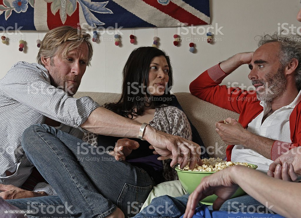 Group of friends in living room, talking and eating popcorn royalty-free stock photo