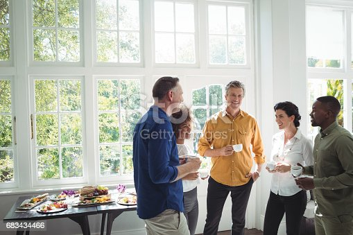 istock Group of friends interacting while having coffee 683434466