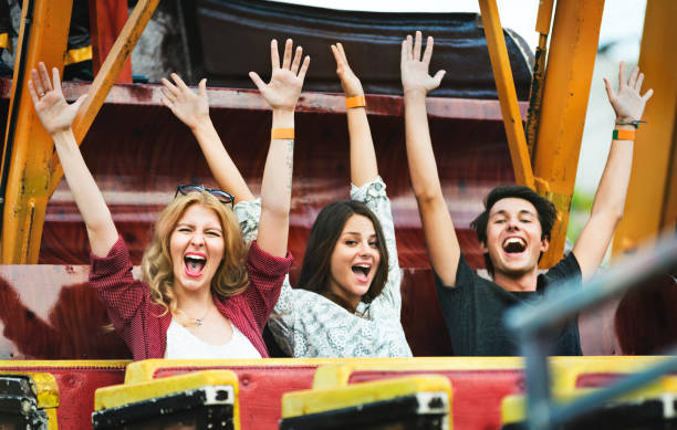 A group of friends is enjoying the amusement park A group of friends is enjoying the amusement park amusement park stock pictures, royalty-free photos & images