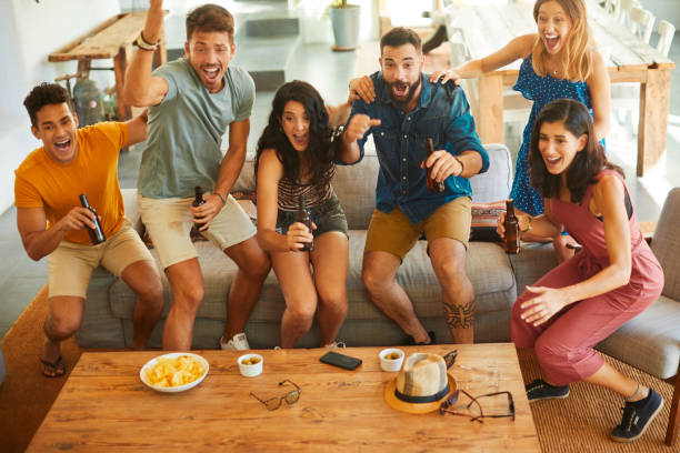 Group of friends jump in joy when their team scores a goal. Friends enjoying time together and partying in a Spanish home. spectator stock pictures, royalty-free photos & images