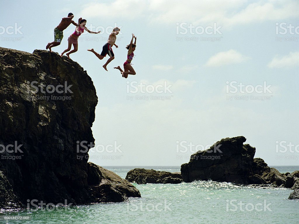 Group of friends jumping into ocean from rock cliff Te Arai Point, North Island, New Zealand. 20-24 Years Stock Photo