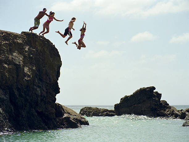 Group of friends jumping into ocean from rock cliff stock photo