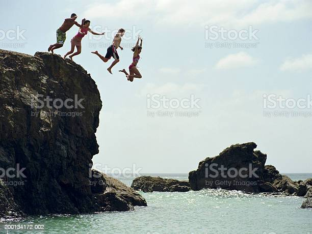 Group Of Friends Jumping Into Ocean From Rock Cliff Stock Photo - Download Image Now