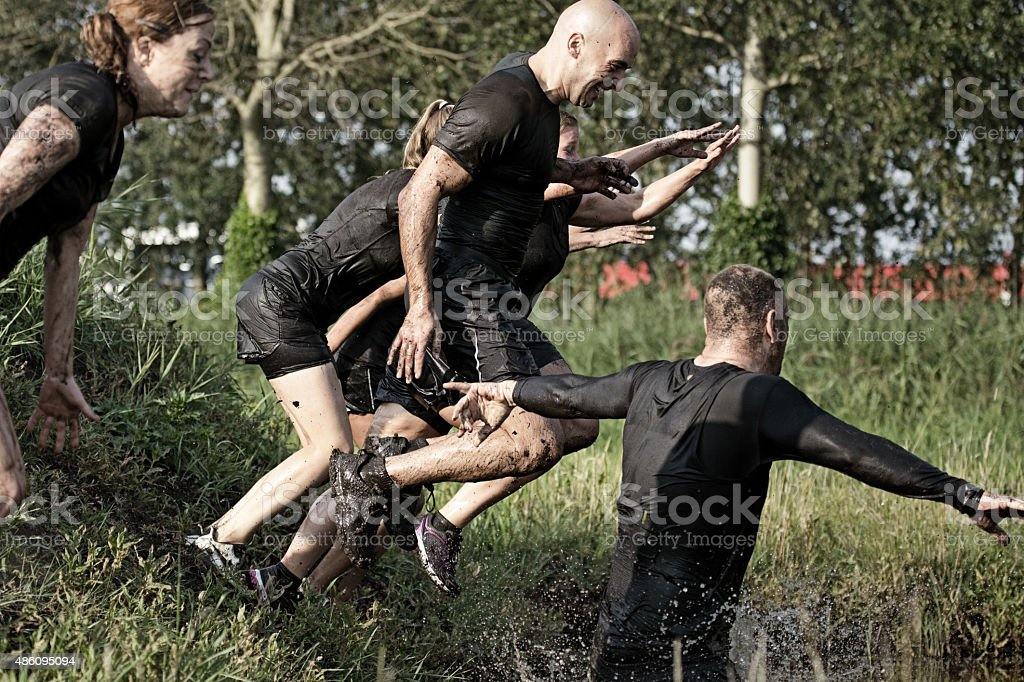 group of friends jumping into water during mud run stock photo