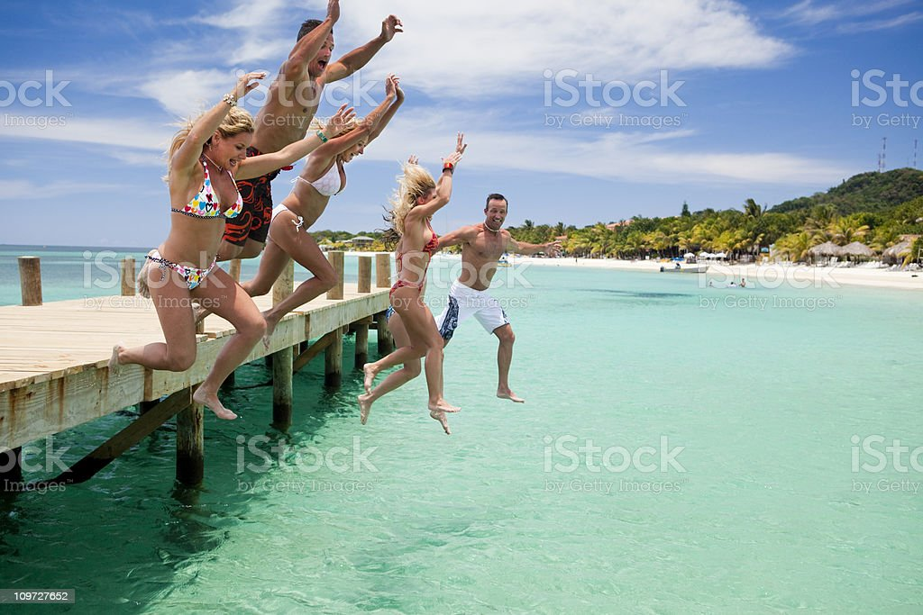 Group of friends jumping off dock royalty-free stock photo
