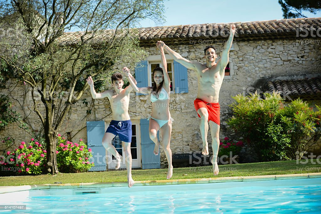 group of friends jumping resorts swimming pool in summer holidays stock photo