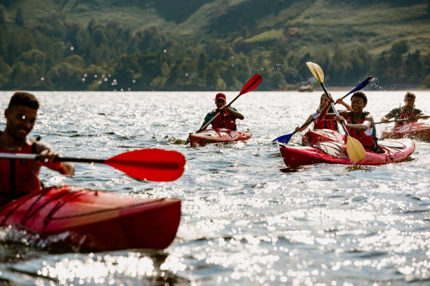 Group of Friends Kayaking A group of friends having fun kayaking on Derwent Water in The Lake District cumbria stock pictures, royalty-free photos & images